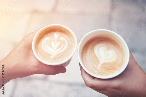 Take-away coffee s in hands with latte art. - 283961184