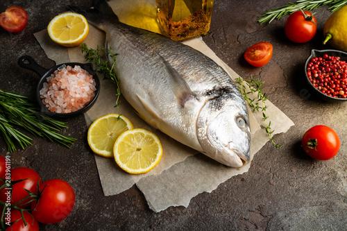 Fotografie, Obraz  Raw fish dorado with lemon, herbs, spices and tomato on dark background