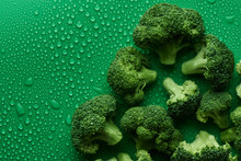 Fresh Raw Broccoli On Green Background With Copy Space, Top View. The Concept Of Healthy Food, Diet, Sulforaphane, Cruciferous Vegetables