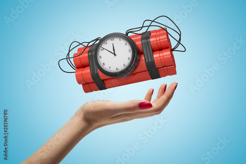 Fotobehang Palm boom Female hand holding red dynamite stick time bomb on blue background