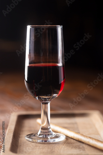 Stampa su Tela Glass of port wine on wooden table and over dark background