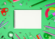 canvas print picture - School accessories and office stationery and emty notrbook on green background.