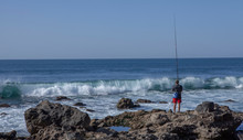 Gran Canaria Spain Maspalomas Beach Ocean Rocks. Man Fishing. Wave. Breakers.