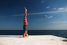 Adult Blond Woman With Short Haircut Practices Yoga On The Pier Against The Background Of The Sea And Blue Sky