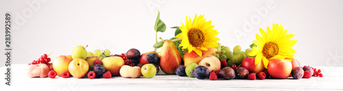 Autumn nature concept. Fall fruit with grapes, plums and sunflower on wood. Thanksgiving dinner - 283992589