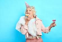 Glamour Old Lady In Party Hat Holding A Glass Of Wine And Eating Yummy Cake. Isolated Blue Background. Studio Shot. People, Happiness