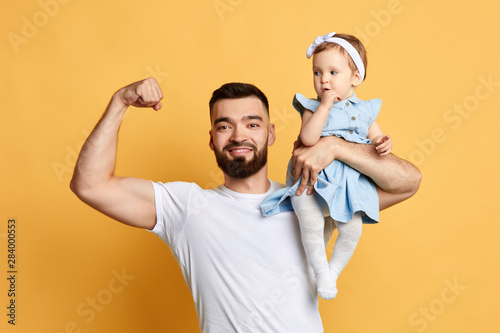 Photo handsome positive father showing his strength, biceps while holding his cute little daughter