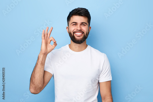 handsome positive bearded man in white T-shirt isolated on blue background showing ok sign Canvas Print