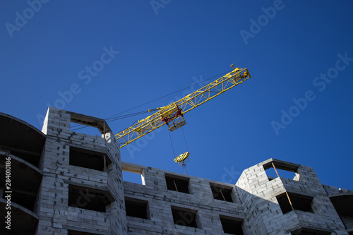 Fotografia  Shot of jib of yellow crane near building partially constructed