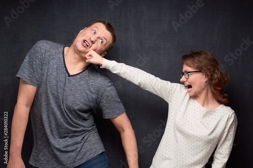 Photo Enraged woman is beating man grimacing from pain