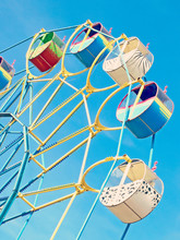 Colorful Ferris Wheel Carousel Against Of The Blue Sky.