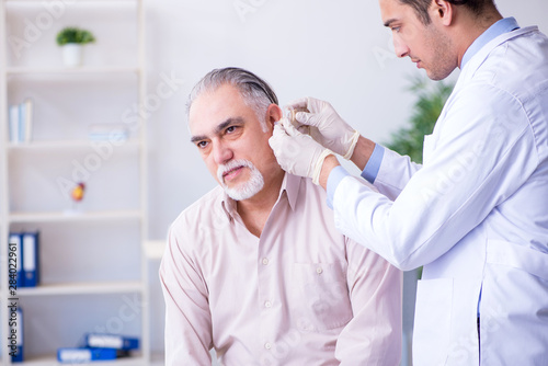 Valokuva  Male patient with hearing problem visiting doctor otorhinolaryng
