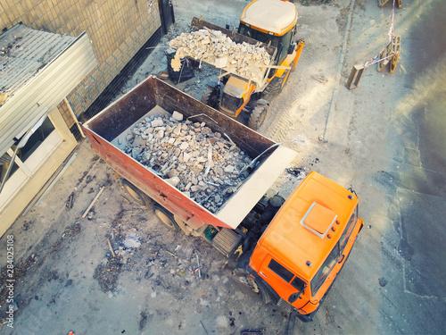 Fotografía Bulldozer loader uploading waste and debris into dump truck at construction site