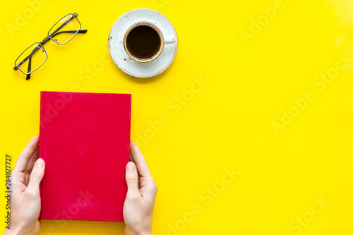 Reading book in hands with glasses and coffee on yellow background top view spac Fototapeta