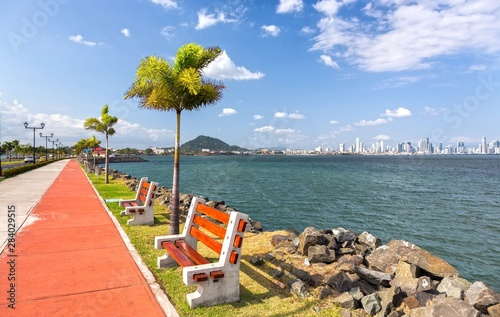 Canvas Prints Palm tree The Amador Causeway road, Panama City famous booming boardwalk and tourist attraction, dotted with park benches and palm trees, with distant city center skyline on horizon