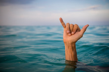 Hand Of Surfer Making Shaka (hang Loose) Sign In Tropical Blue Waters