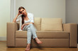 Tired woman in depression sitting on sofa