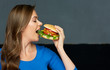 canvas print picture - young woman eating big cheeseburger.