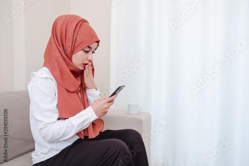 Pinturas sobre lienzo  Muslim girl use smart phone and she shocked, girl is taken aback or surprised