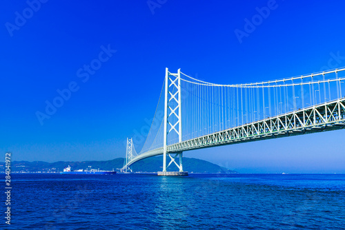 Foto op Plexiglas Donkerblauw Landscape of Akashi Kaikyo Bridge in the background of blue sky in the summer morning