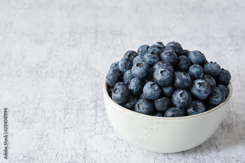 Photo Fresh blueberries in a white ceramic bowl on a light gray crackle background