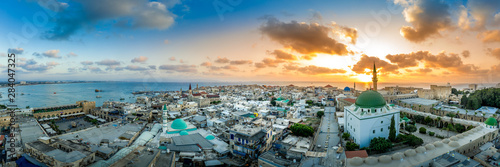 Aerial sunset view of Acco medieval old city with Al Jazzar mosque crusader and Ottoman city walls, arab bazaar and orange sky