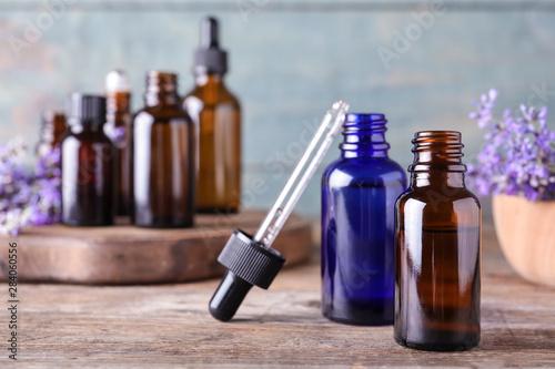 Fototapeta Bottles of lavender essential oil and flowers on wooden table against blue background obraz