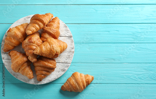 Fototapeta Board with tasty croissants and space for text on light blue background, flat lay. French pastry obraz