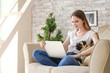 Beautiful young woman with cute pug dog working on laptop at home