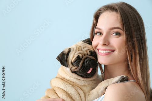 Obraz Beautiful young woman with cute pug dog on color background - fototapety do salonu