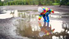 Child Walking In Wellies In Puddle On Rainy Weather