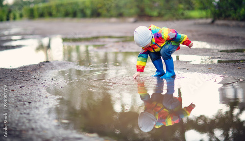Fototapeta Child walking in wellies in puddle on rainy weather