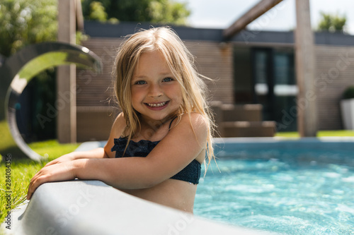 Mirthful girl in swimsuit relaxing in the pool and smiling Canvas Print