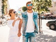 Smiling beautiful girl and her handsome boyfriend posing in the street. Woman in casual summer dress and man in jeans clothes. Happy cheerful couple family having fun in sunglasses