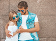 Leinwandbild Motiv Smiling beautiful girl and her handsome boyfriend. Woman in casual summer dress.Man in jeans clothes.Happy cheerful family.Female having fun on the street near wall.Hugging couple in sunglasses
