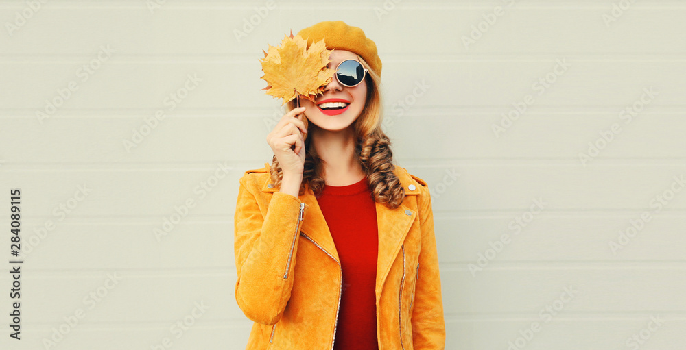 Fototapety, obrazy: Autumn mood! happy smiling woman holding in her hands yellow maple leaves hiding her eye over gray wall background