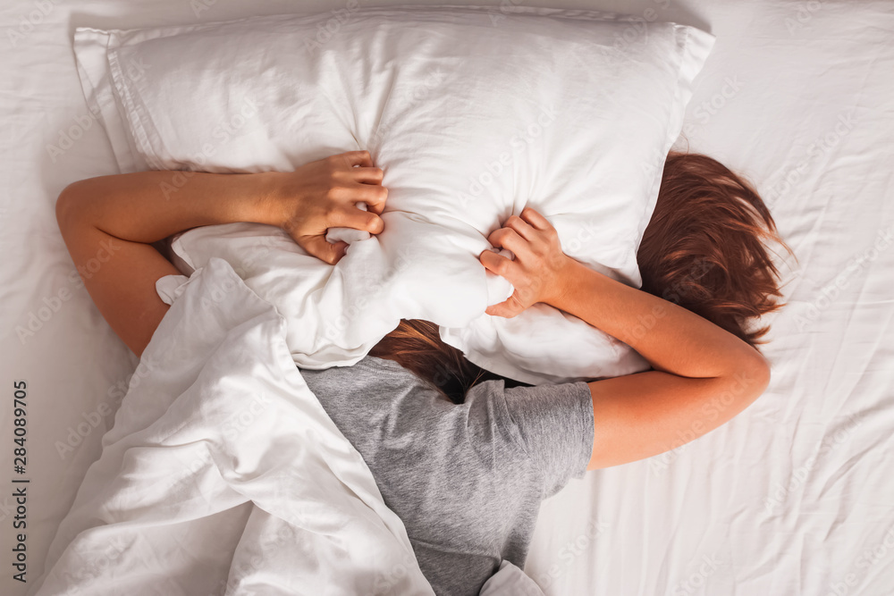 Fototapeta Woman lying in bed and covering her head with pillow.