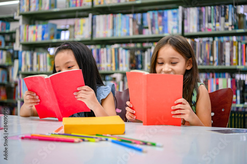 Fotografija  Happiness two cute diversity girls reading book in school library funny