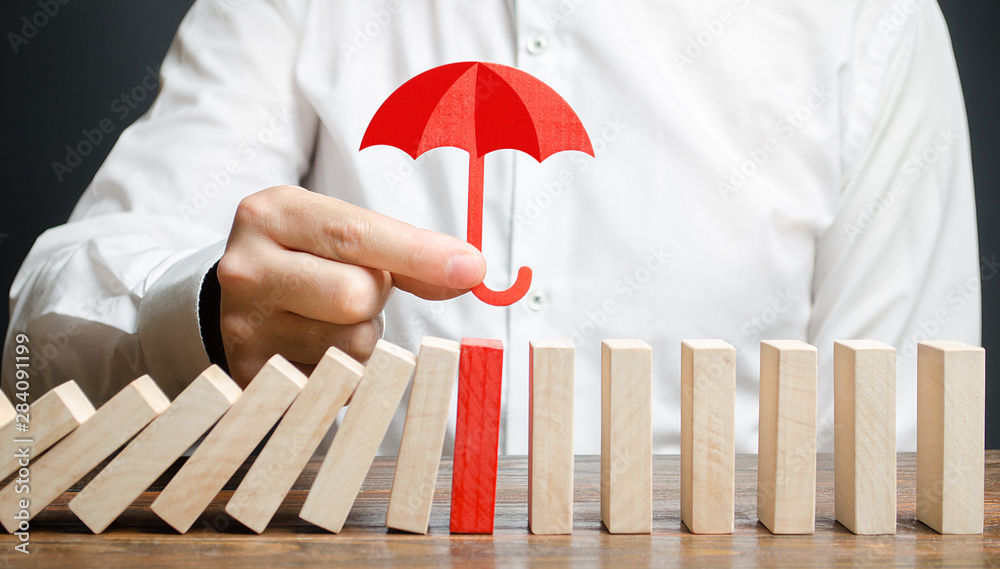 Fototapeta A businessman insures red dominoes and stops the collapse of the whole system. Insurance and risk management. Accurate forecasts and miscalculations. Financial support, subsidies and exemptions
