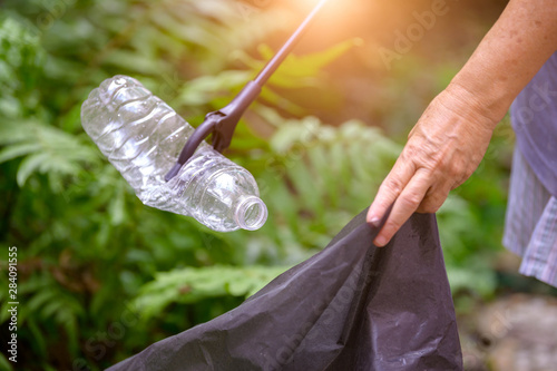 Valokuva  Closeup of hand and waste grabber picking up drinking plastic bottle waste into bag