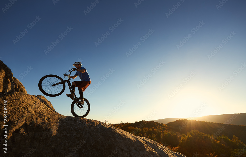 Fototapety, obrazy: Silhouette of professional cyclist riding on back wheel on trial bicycle. Sportsman rider making trick on the edge of rock on the top of mountain at sunset. Concept of extreme sport active lifestyle