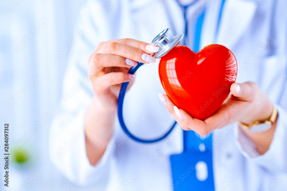 Fototapety, obrazy: Female doctor with stethoscope examining red heart. Health, medicine, people and cardiology concept