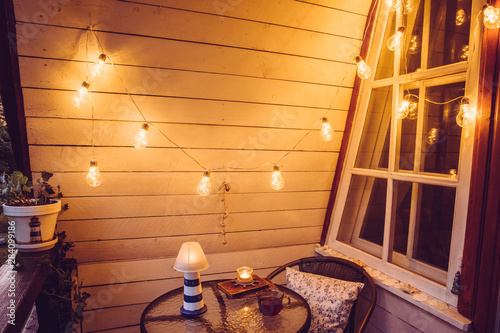 Fotografia Cute retro wooden nautical style balcony view with small garden table and chair and decorative string party bulbs lights on in the evening