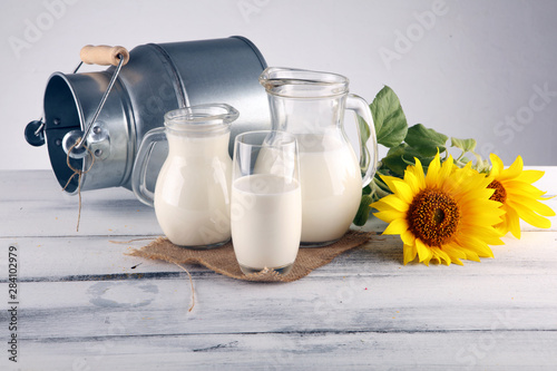 Obraz na plátně A jug of milk and glass of milk on a wooden table and flower