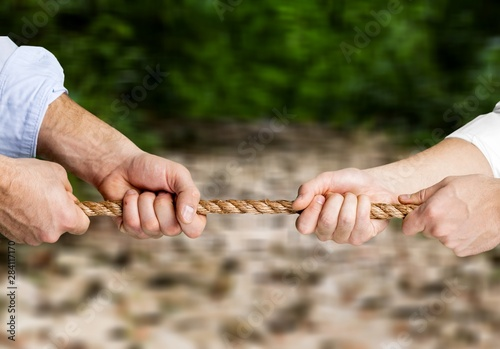 Poster de jardin Montagne Business people pulling rope in opposite directions at office
