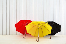 Three Umbrellas On Floor Near White Wooden Wall With Space For Design