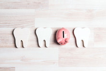 Pink Piggy Bank With Teeth On A Light Wooden Background.