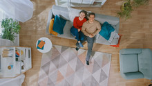 Young Beautiful Couple Is Lying Down On Sofa. Cozy Living Room With Modern Interior With Plants, Table And Wooden Floor. Top View.