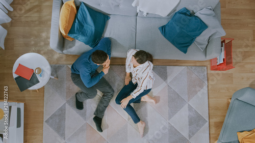 Photo  Young Couple is Sitting on a Floor and Talking