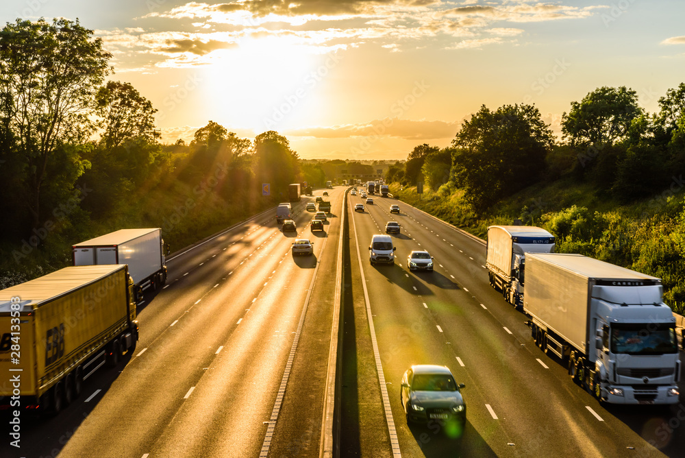 Fototapeta busy traffic on uk motorway road overhead view at sunset